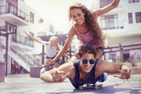 Playful young couple riding skateboard