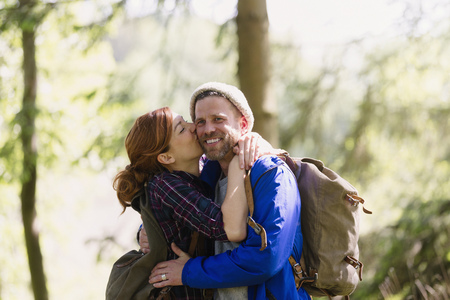 looking away from camera: Portrait smiling couple kissing hiking in woods