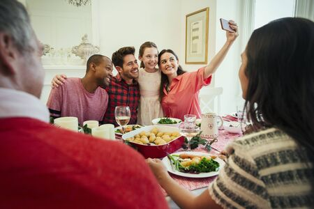 Multi-ethnic family with camera phone taking selfie at Christmas dinner table