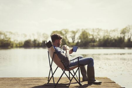 Man drinking coffee and using digital tablet on sunny lakeside dock