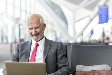business: Businessman working using laptop in airport departure area