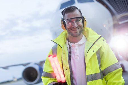 traffic controller: Portrait smiling air traffic controller in front of airplane on tarmac