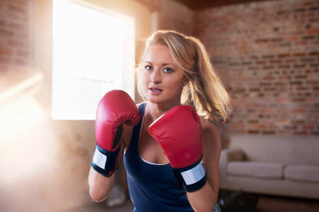 boxing day: Portrait tough young woman boxing in studio LANG_EVOIMAGES