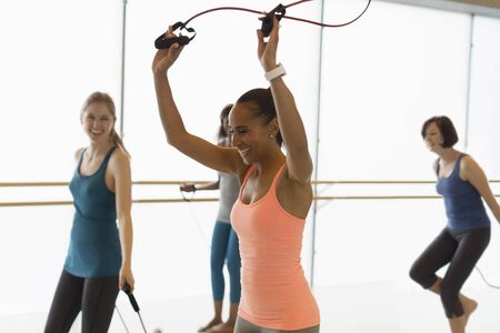 Smiling women jumping rope in exercise class gym studio