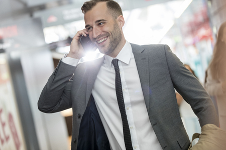 business: Smiling businessman talking on cell phone in airport