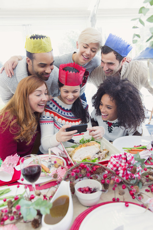 Friends in paper crowns taking selfie at Christmas dinner LANG_EVOIMAGES