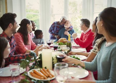 Affectionate multi-ethnic senior couple hugging at family Christmas dinner table