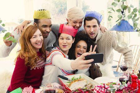 vietnamese ethnicity: Friends wearing paper crowns taking selfie at Christmas dinner LANG_EVOIMAGES
