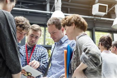 information medium: Business people using digital tablet at technology conference LANG_EVOIMAGES