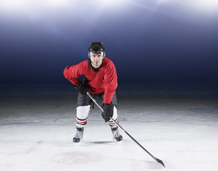 padding: Portrait determined hockey player in red uniform on ice