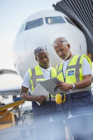 traffic controller: Air traffic controllers with clipboard below airplane on airport tarmac