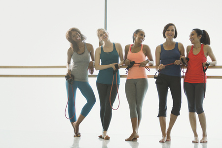 jamaican adult: Portrait smiling women with resistance bands at barre in exercise class gym studio