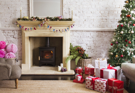 Christmas tree, gifts and decorations near fireplace in living room LANG_EVOIMAGES