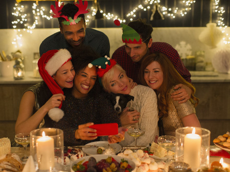lady on phone: Playful friends with dog taking selfie at candlelight Christmas table