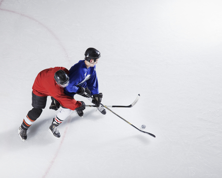 Hockey players going for puck on ice LANG_EVOIMAGES