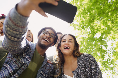 lady on phone: Enthusiastic friends taking selfie with camera phone below tree