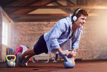 mp3 player: Determined young man with headphones doing push-ups with kettlebell