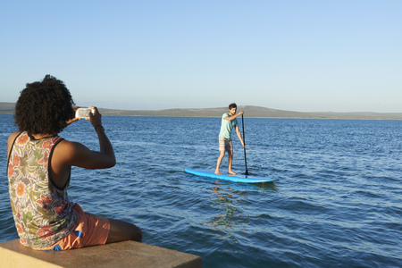 paddles: Young man photographing friend paddleboarding on sunny summer ocean LANG_EVOIMAGES