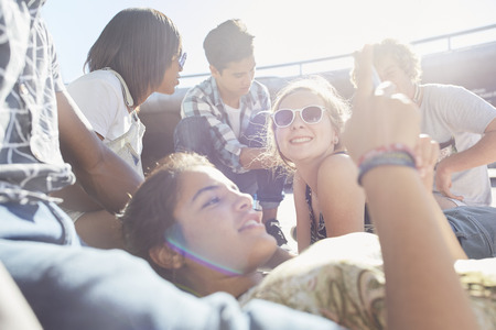 looking away from camera: Teenage friends hanging out texting on sunny day LANG_EVOIMAGES