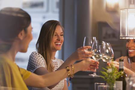 jamaican adult: Smiling women friends toasting white wine glasses dining in restaurant