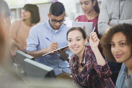 vocational high school: College student raising hand in computer lab classroom