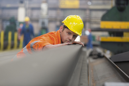 Steel worker examining steel in factory LANG_EVOIMAGES