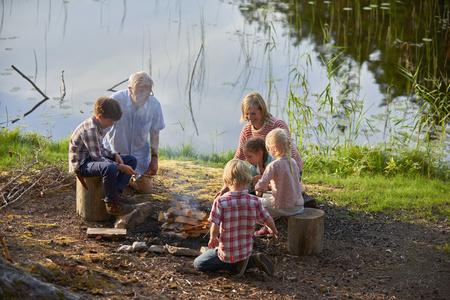 arrodillarse: Abuelos y nietos disfrutando de una fogata en la orilla del lago LANG_EVOIMAGES