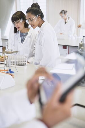 College students conducting scientific experiment in science laboratory classroom