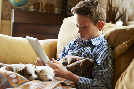 Boy using digital tablet with puppies in lap
