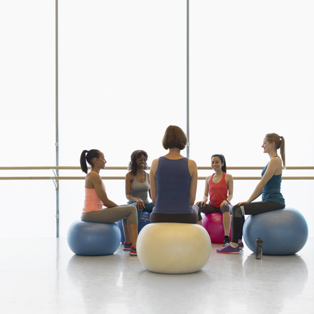 jamaican adult: Women on fitness balls in circle in exercise class gym studio