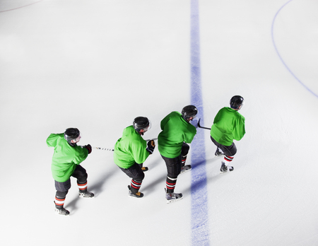 padding: Hockey team in green uniforms skating in a row on ice LANG_EVOIMAGES