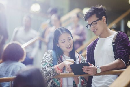 standing up: College students using digital tablet in stairway