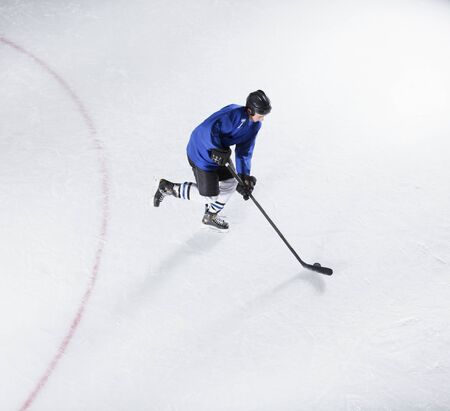 padding: Hockey player in blue uniform skating with puck on ice