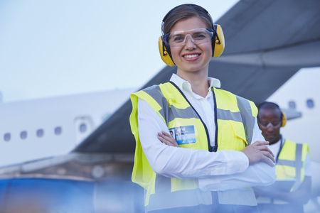 traffic controller: Portrait smiling female air traffic controller standing near airplane