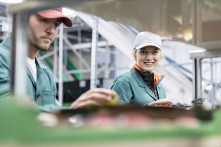 le cap: Portrait smiling female worker inspecting apples in food processing plant