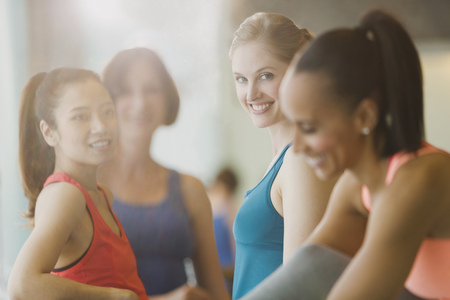 jamaican adult: Smiling women talking in sunny gym studio LANG_EVOIMAGES