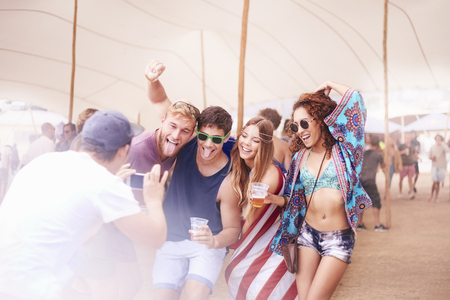 lady on phone: Playful young friends with beer posing for camera phone at music festival