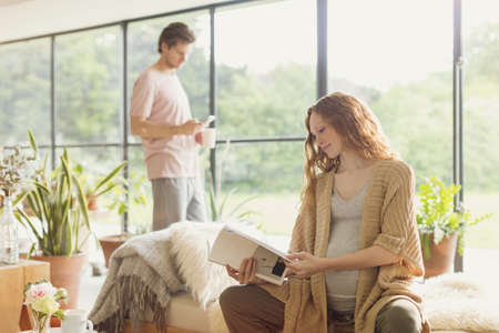 sunroom: Pregnant woman reading book in living room