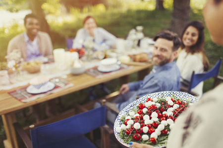 vietnamese ethnicity: Woman serving Caprese salad appetizer to friends at patio table