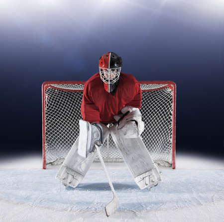 padding: Portrait determined hockey goalie protecting goal net on ice