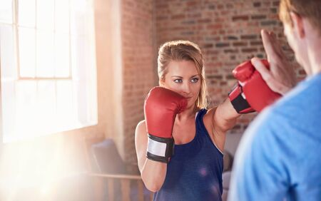 punched out: Young female boxer practicing boxing with trainer in gym studio