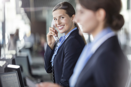 lady on phone: Portrait smiling customer representative talking on telephone at airport check-in counter