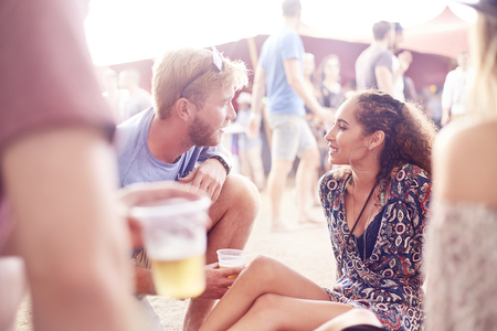 Young couple drinking beer and talking at music festival LANG_EVOIMAGES