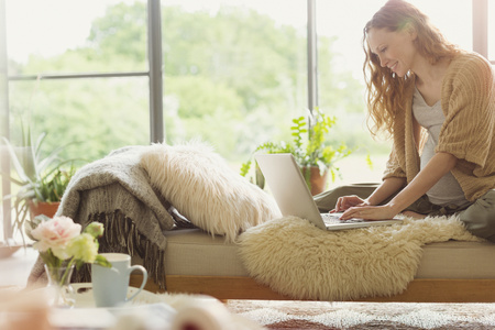 sunroom: Pregnant woman using laptop on chaise lounge in living room LANG_EVOIMAGES
