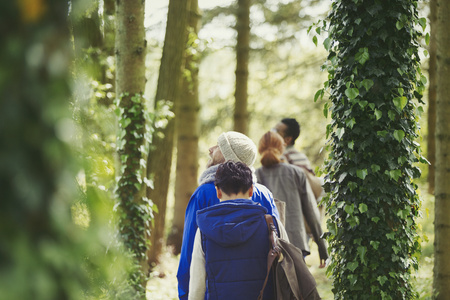 vietnamese ethnicity: Friends hiking among ivy covered trees in woods