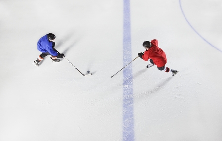 padding: Overhead view hockey players going for puck on ice LANG_EVOIMAGES
