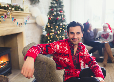 fireplace living room: Portrait smiling man in Christmas sweater sitting in living room LANG_EVOIMAGES