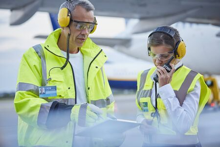 traffic controller: Air traffic control ground crew workers with clipboard talking on airport tarmac