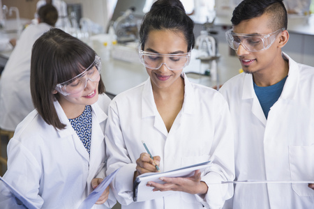 vocational high school: College students in lab coats discussing notes in science laboratory classroom