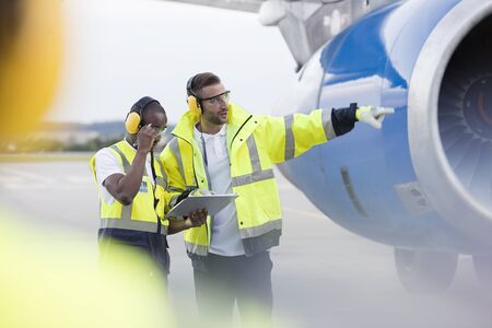 traffic controller: Air traffic controllers with clipboard next to airplane on airport tarmac